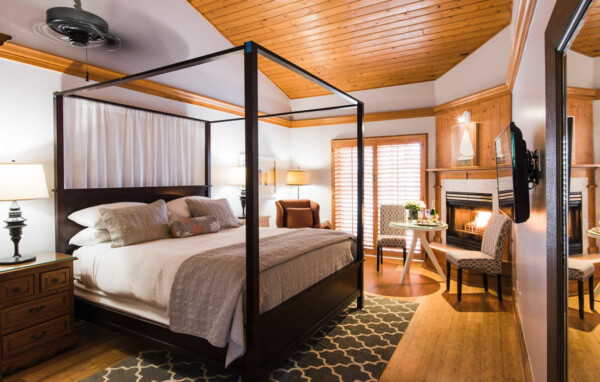 santa barbara coast hotel guest room with bed, table and chairs plus fireplace